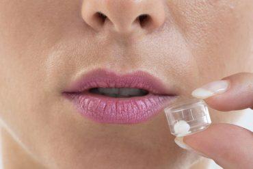 38426704 - young woman tacking homeopathy pills