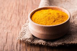 36477009 - dry spice turmeric in a wooden bowl close-up on a vintage background