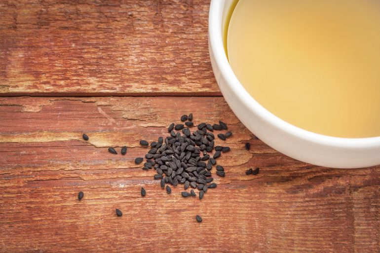 67789459 - black cumin seeds (nigella sativa) and oil in a small bowl against rustic bran wood